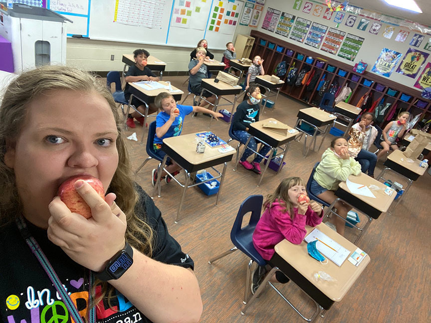 teacher and class eating apples
