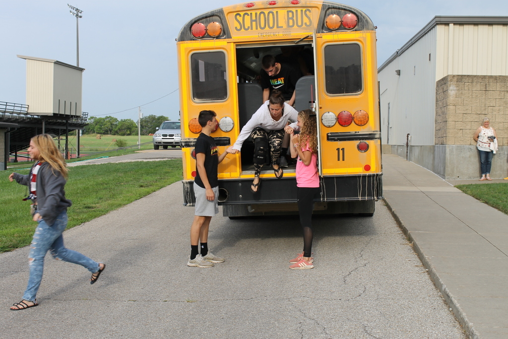 kids jumping out of the back door of the bus