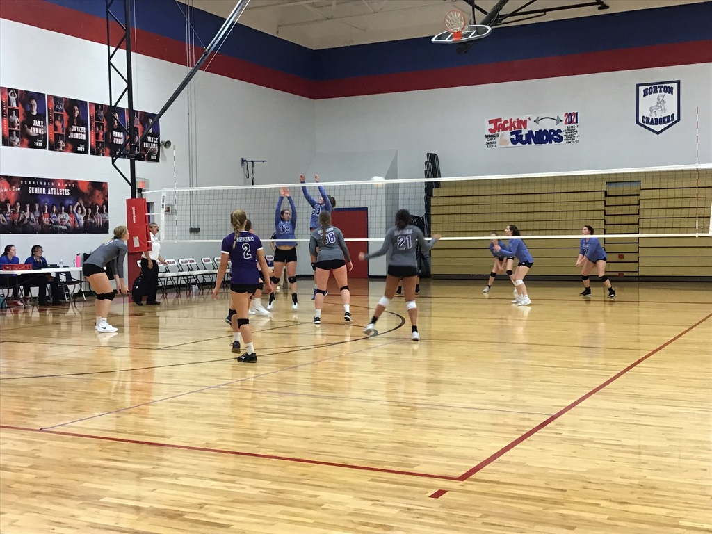 JV volleyball players at the net