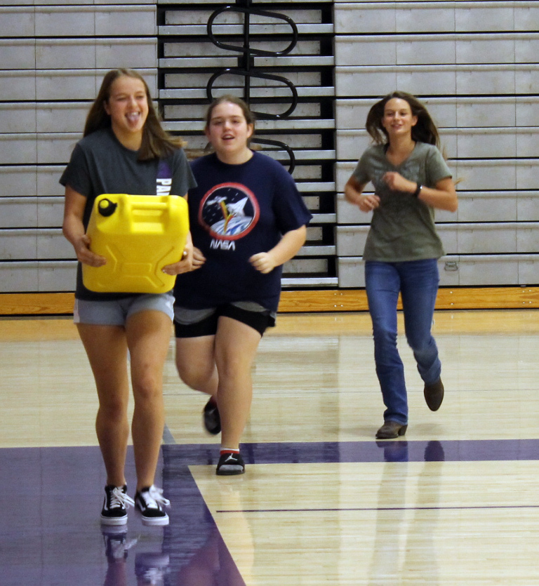 students carrying 5-gallon water jug